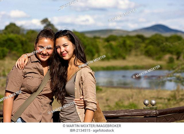 Two girls, about 13 and 18, wearing safari outfits leaning against on a railing, Masai Mara National Reserve, Kenya, East Africa, Africa, PublicGround