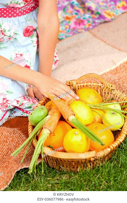 Closeup shot of girl sitting on grass and taking carrot out of basket