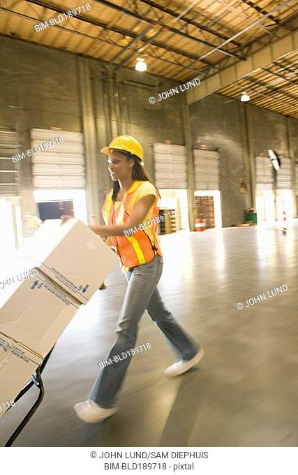 Female warehouse working pushing boxes on hand truck