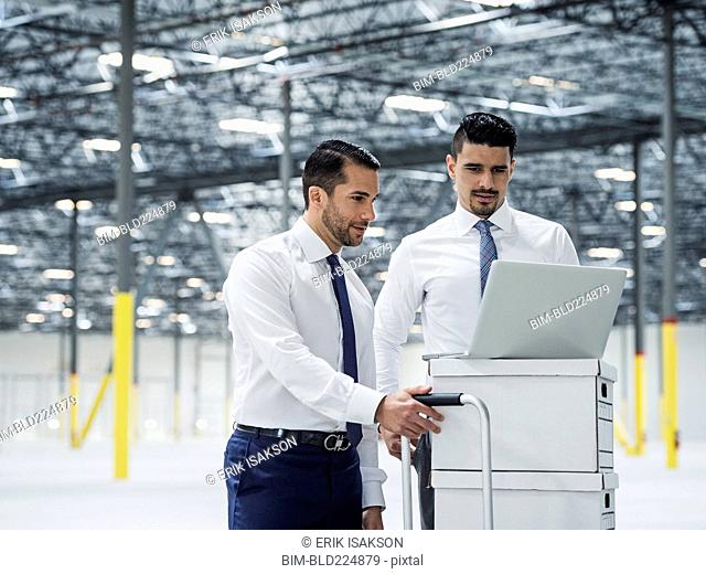 Businessmen using laptop on cardboard boxes in warehouse