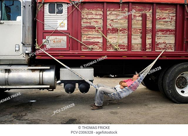 Mexico, Truck Driver Sleeping In Hammock Attached To His Truck; Aguascalientes