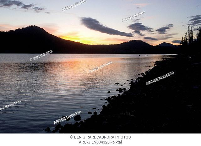 Elk Lake at dusk with silhouettes of forested hills in background, Oregon, USA