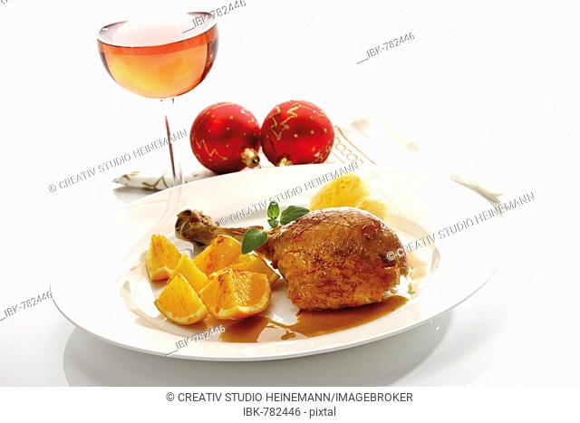 Roast turkey drumstick served on a white plate with orange slices, pear and gravy beside Christmas decorations