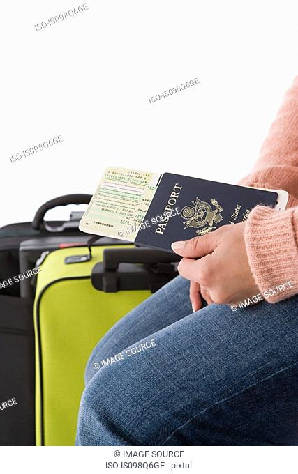 A woman holding a passport and airplane tickets