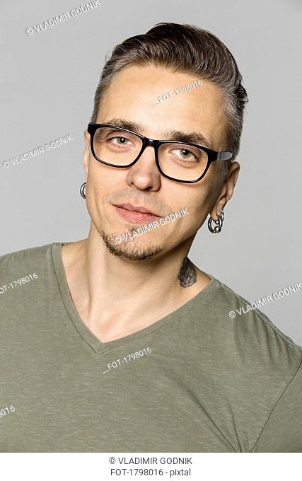 Portrait of man with glasses against gray background