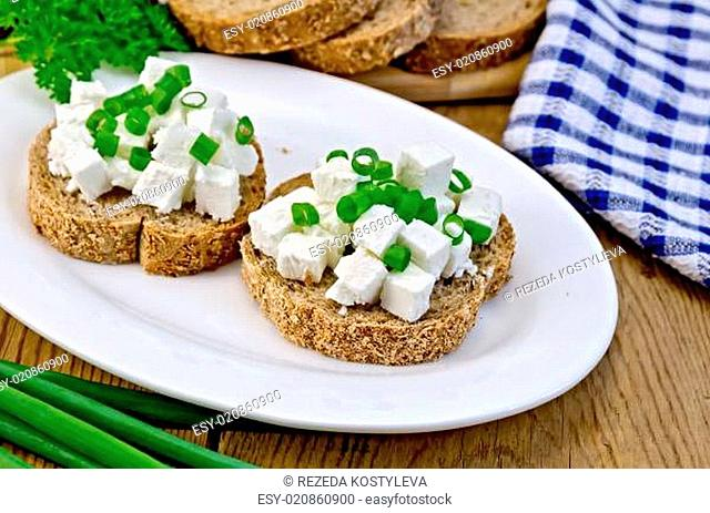Bread with feta cheese and green onions on a board