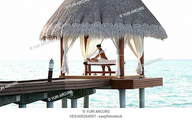 Woman receiving a massage in a luxury gazebo at the end of a jetty with the ocean in the background
