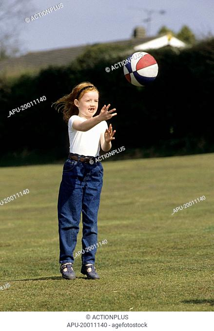 Little girl playing with ball on field