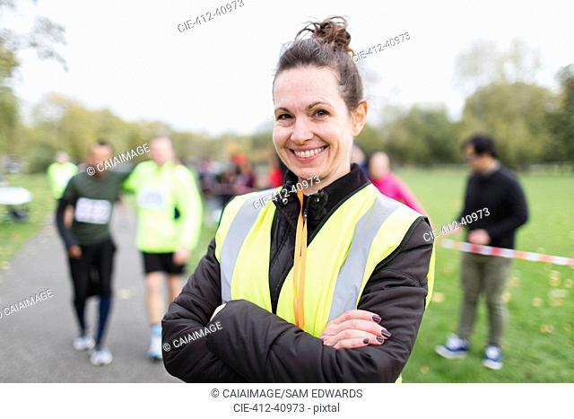 Portrait smiling female volunteer at charity run in park
