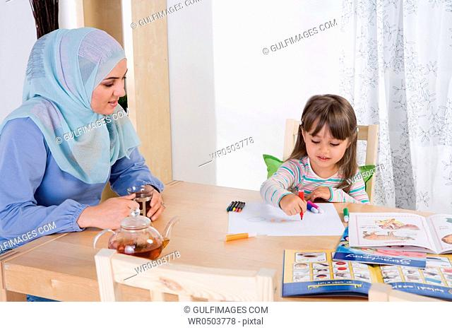 Arab mother helping her daughter with homework