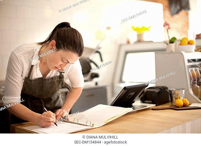 Woman taking notes while speaking on phone