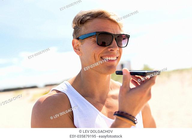 summer holidays, technology and people concept - happy smiling young man in sunglasses using voice command recorder on smartphone on beach