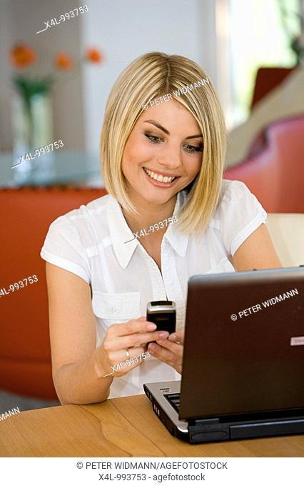 woman using notebook and mobilphone at home