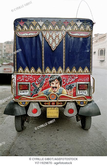 Painting of a man with guns on the back of a decorated auto-rickshaw, Peshawar, North-West Frontier Province, Pakistan, Indian Sub-Continent, Asia