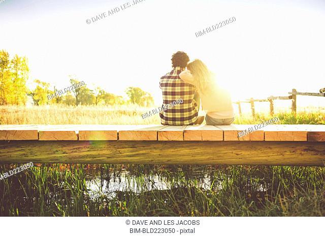 Hispanic couple sitting on footbridge over marsh