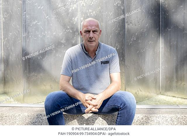 27 August 2019, Berlin: Mario Basler, former professional soccer player, is sitting in front of a water wall in the courtyard of a hotel in front of an...