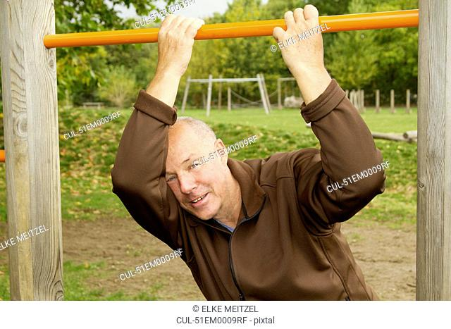 Older man hanging from jungle gym