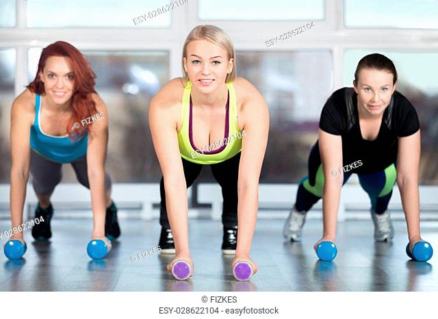 Fitness practice, group of three cheerful smiling beautiful fit young females working out in sports club, doing plank exercise, using dumbbells in class