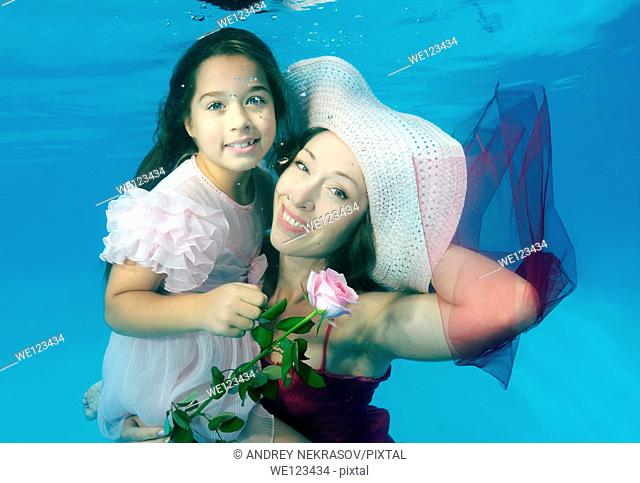 Woman and girl, underwater models, presenting fashion in pool