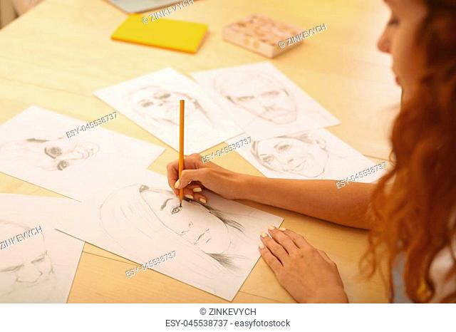 Drawing caricatures. Red-haired appealing creative person feeling extremely cheerful while drawing caricatures