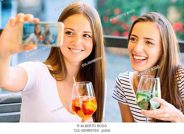 Two young female friends taking smartphone selfie at sidewalk cafe