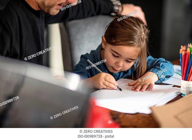 Young man and his daughter drawing at table