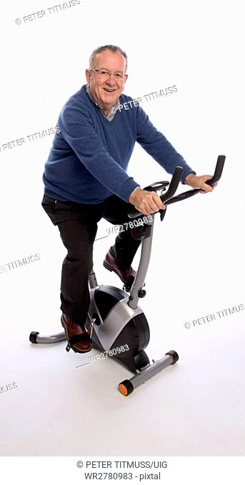 An elderly man trying out an exercise bicycle