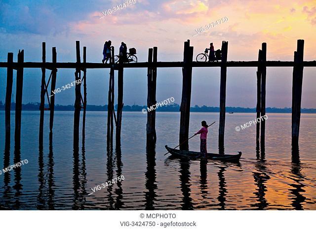 The BURMESE use the teak U BEINS BRIDGE to commute across the Taungthaman Lake at sunrise - AMARAPURA, MYANMAR - 02/05/2012