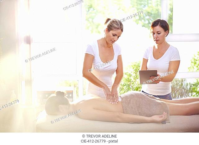 Masseuses with digital tablet massaging woman's back