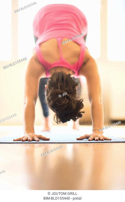 Close up of Hispanic woman practicing yoga in studio