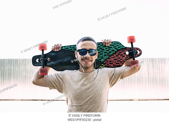 Portrait of confident young man with earbuds carrying longboard
