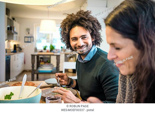 Happy couple eating together pizza and pasta