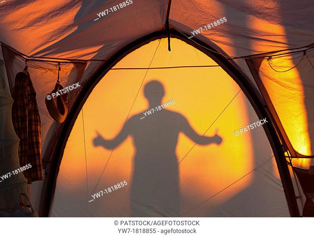 Silhouette of man gesturing ok reflected on a tent