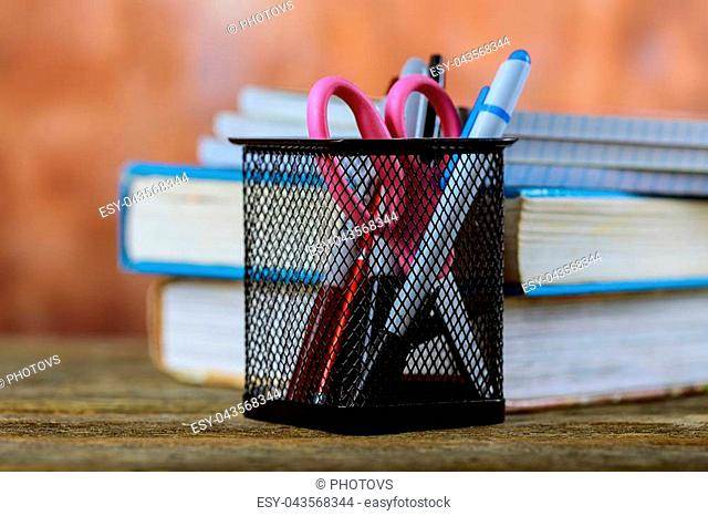 Group of school supplies and books over a wood background