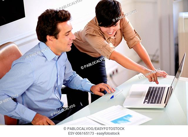 Portrait of an attractive manager talking with his secretary while looking at laptop on office desk