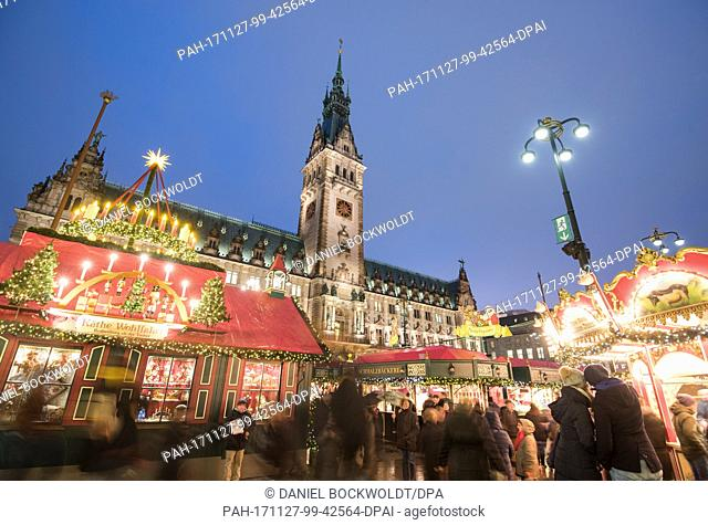 At dusk visitors walk across the grounds of the Roncalli Christmas market on the town hall market place in Hamburg, Germany, 27 November 2017