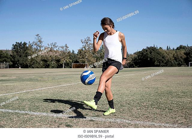 Woman on football pitch playing football