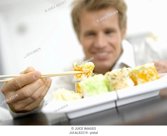 Man using chopsticks on sushi