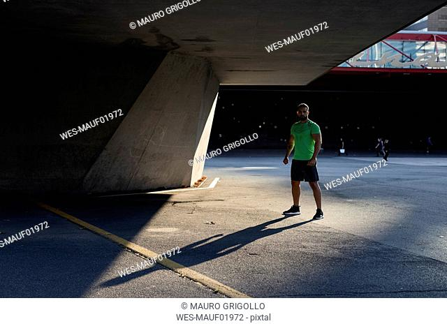 Sportive man during workout, standing on concrete floor