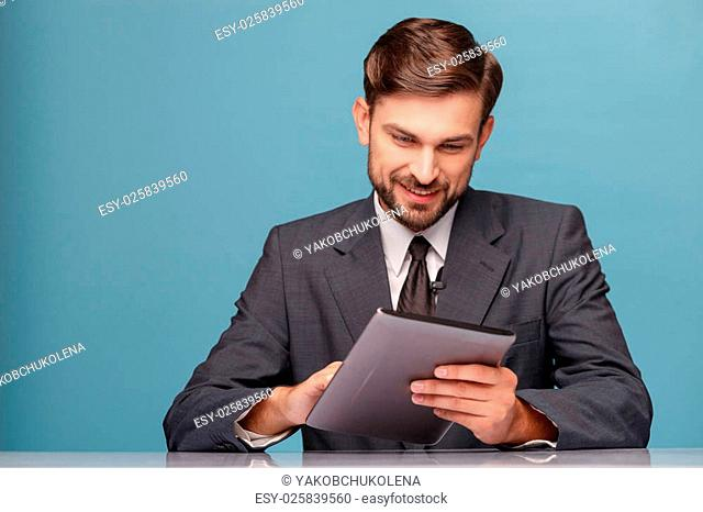 Attractive young anchorman is using a tablet. He is sitting at desk and smiling. Isolated on blue background