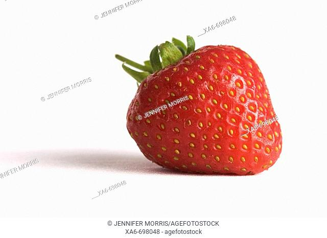 Ripe, red strawberry lying on its side on a white background
