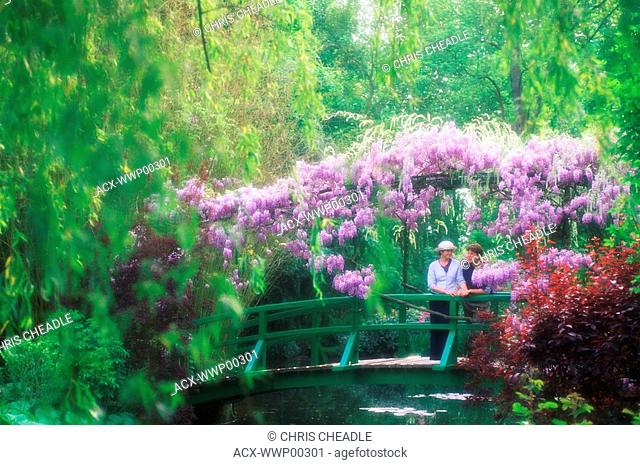 France, Giverney - Monet's Garden - Diffuse woman on bridge with wisteria in full bloom