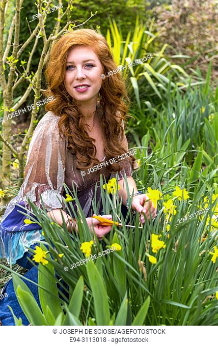 A pretty 25 year old redheaded woman in a garden setting looking at the camera