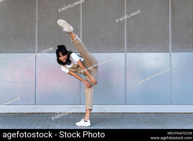 Smiling woman kicking on footpath