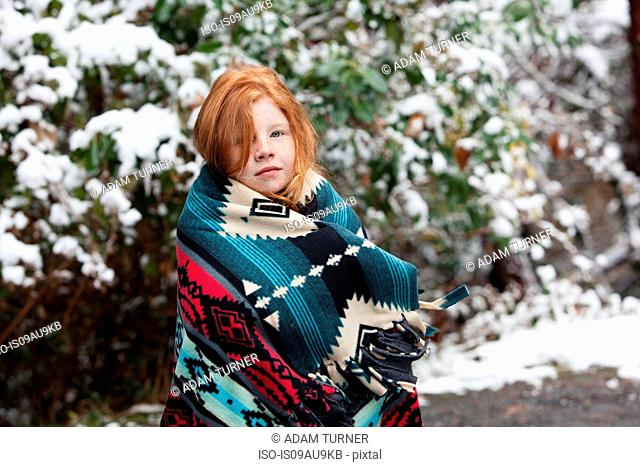 Red haired girl in front of snow covered trees, wrapped in aztec pattern blanket looking at camera