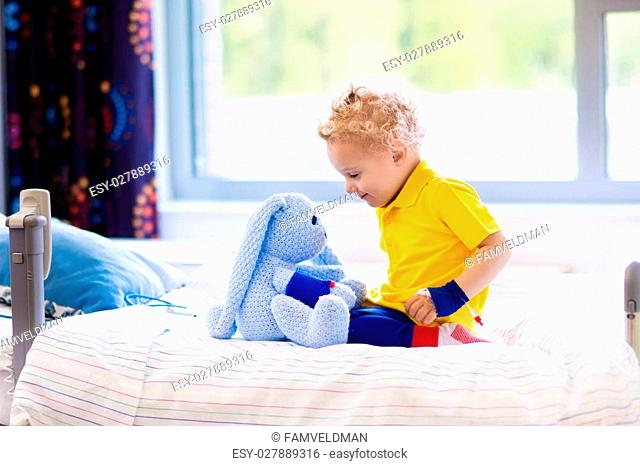 Little boy playing with his toy in bed in hospital room. Child with IV tube and pulse oximeter in modern clinic. Kid recovering from sickness