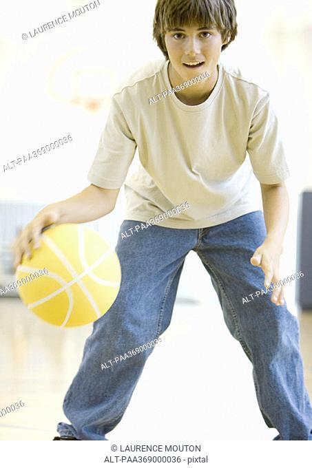 Teenage boy playing basketball