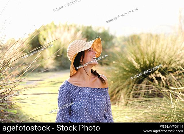 Cheerful young woman looking away while wearing sun hat at countryside