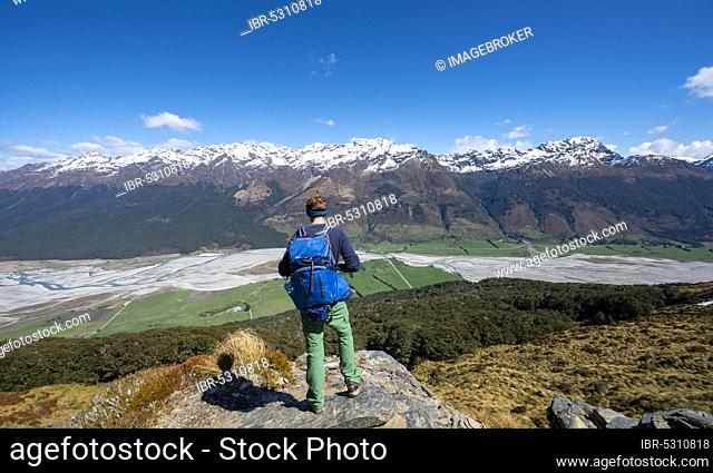 Hiker on the summit of Mount Alfred, view of Dart RIver and mountain range, Glenorchy near Queenstown, Southern Alps, Otago, South Island, New Zealand, Oceania