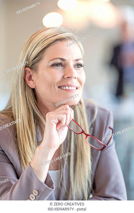 Portrait of smiling mid adult businesswoman holding spectacles